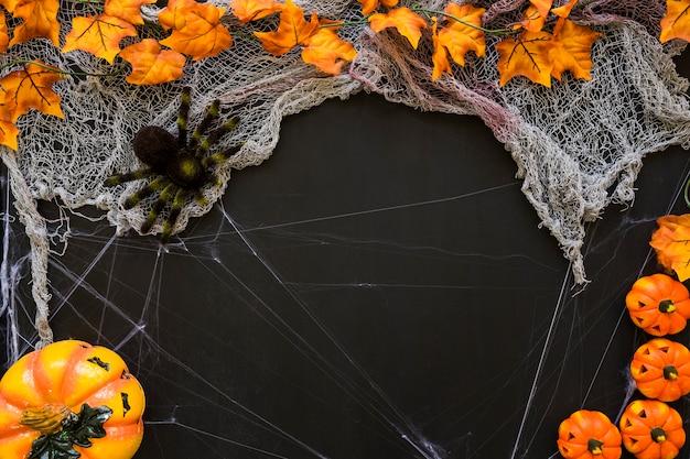 Dark halloween background with pumpkins and spider