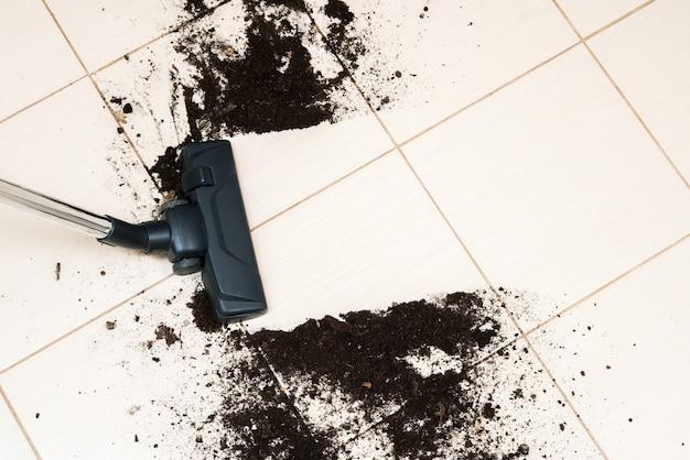 Dark head of a modern vacuum cleaner being used while vacuuming dirt on the floor.