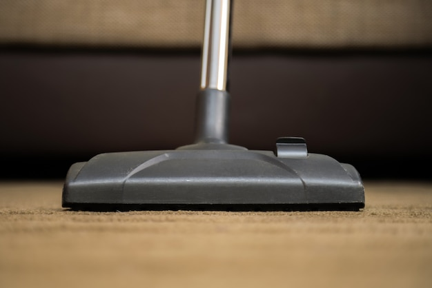 Dark head of a modern vacuum cleaner being used while vacuuming a rug.