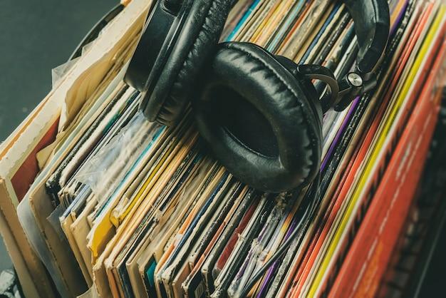 어두운 헤드폰은 복고 비닐 레코드의 스택에 누워 b