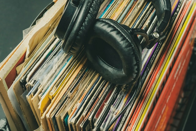 Dark headphones lay on stack of retro vinyl records b