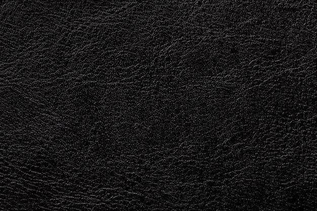Dark ink leather texture background, closeup. black cracked backdrop from wrinkle skin