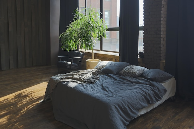 Dark interior of a modern stylish huge open-plan loft-style studio apartment with columns and high ceilings.