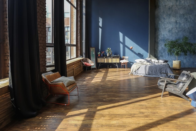 기둥과 높은 천장이있는 현대적이고 세련된 대형 오픈 플랜 로프트 스타일의 스튜디오 아파트의 어두운 인테리어.