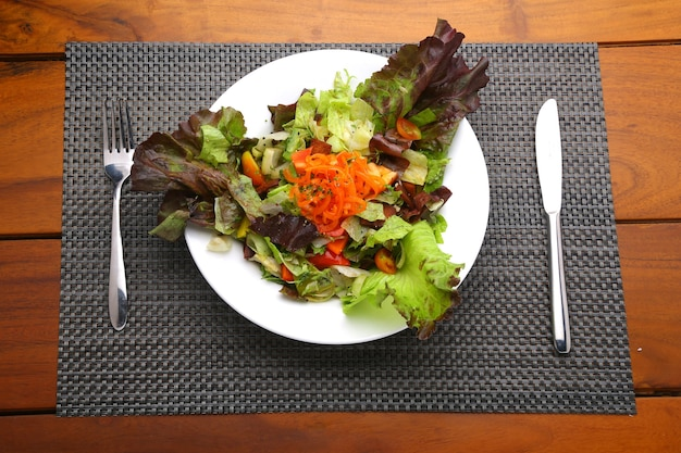 어두운 잎이 많은 녹색 채소 샐러드 하얀 접시에 배열된 건강한 잎이 많은 샐러드