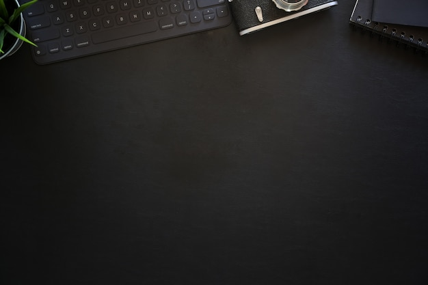 Dark leather office photography desk table with keyboard tablet and vintage camera