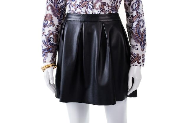 마네킹에 어두운 가죽 스커트. 여성용 골드 팔찌와 스커트. 주름이 있는 검은색 치마. 고품질 의류 및 보석.