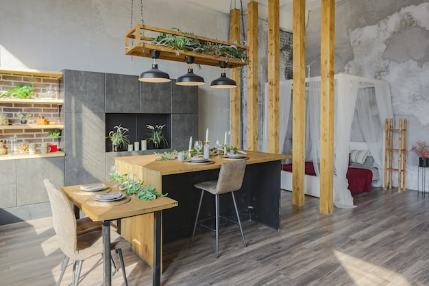 Dark loft style interior of big cozy country house. open plan apartment with kitchen area, rest zone and bed area. huge windows and wooden decoration