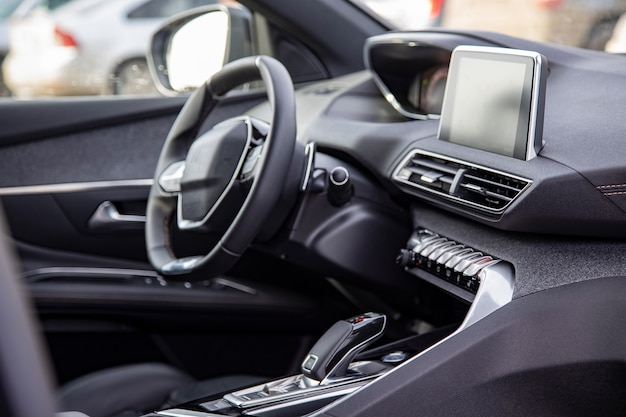 Dark luxury car interior. black leather multifunctional steering wheel, start and stop engine buttom, dashboard, steering wheel and driver seat