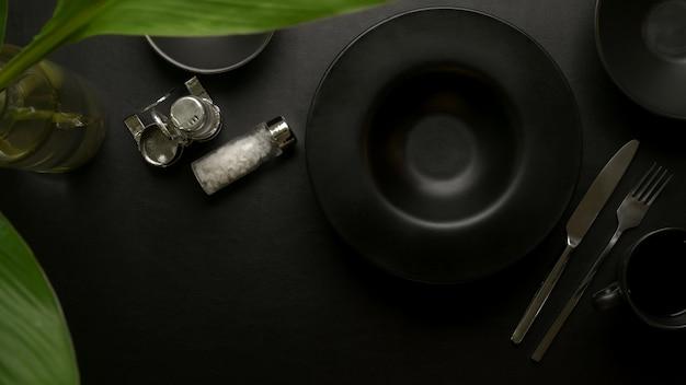 黒のセラミックプレート、銀器、調味料のボトル、コピースペース、植物の花瓶を備えたダークラグジュアリーのダイニングテーブル