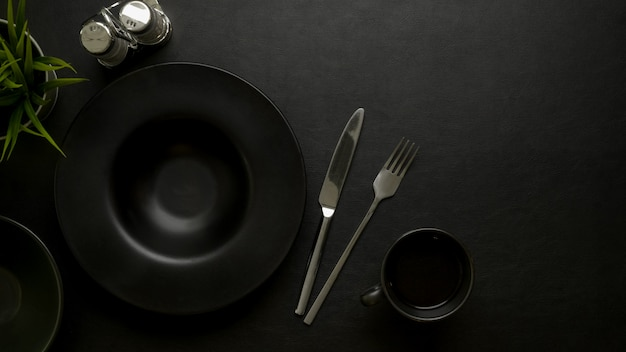 Dark luxury dinning table setting with black ceramic plate, silverware, seasoning bottles, copy space and decoration