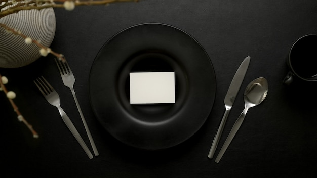 Dark luxury dinning table setting with  place cacd on black ceramic plate, silverware and decoration