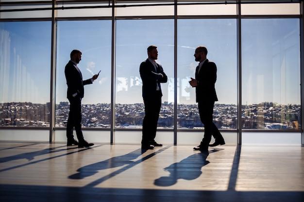 파노라마 창의 배경에 어두운 남성 실루엣. 대도시가 내려다보이는 고층 빌딩의 큰 창 밖을 바라보는 남성 사업가들