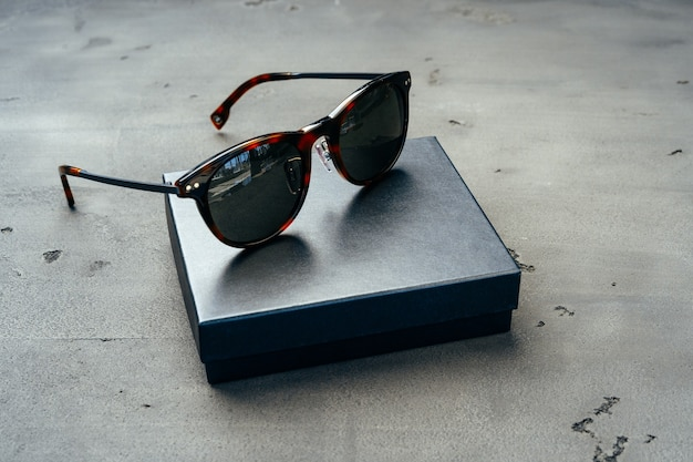 Dark male sunglasses on grey concrete