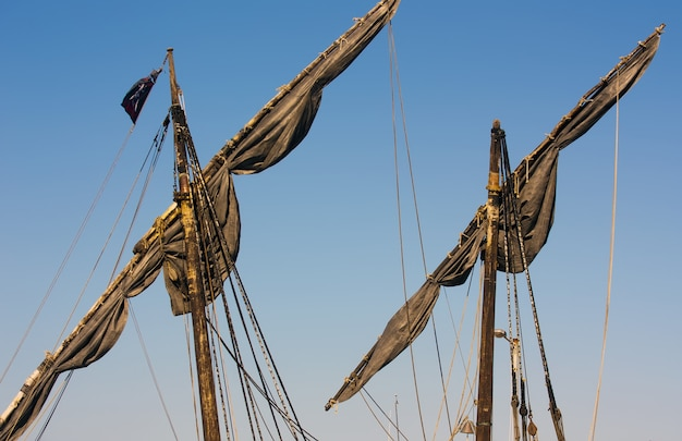 Dark masts of a ship with the sky in the background