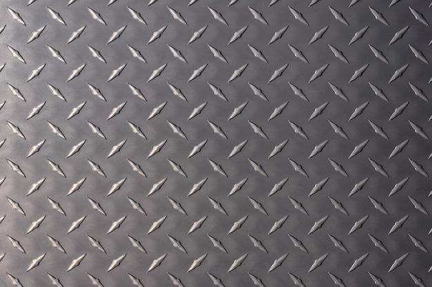 배경으로 어두운 금속 접시입니다. 마름모 패턴으로 강철 텍스처입니다.
