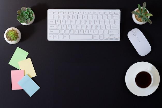 コンピューター、マウス、空白のステッカー、植物、一杯のコーヒーと暗い近代的なオフィスデスクテーブル。コピースペースの平面図