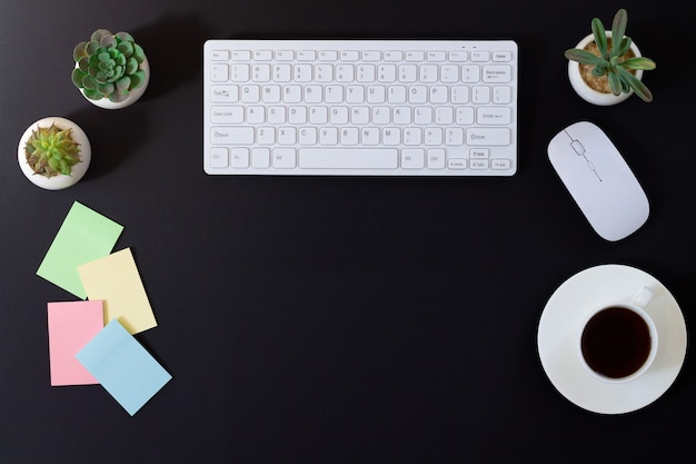 Dark modern office desk table with computer, mouse, blank stickers, plants and cup of coffee. top view with copy space