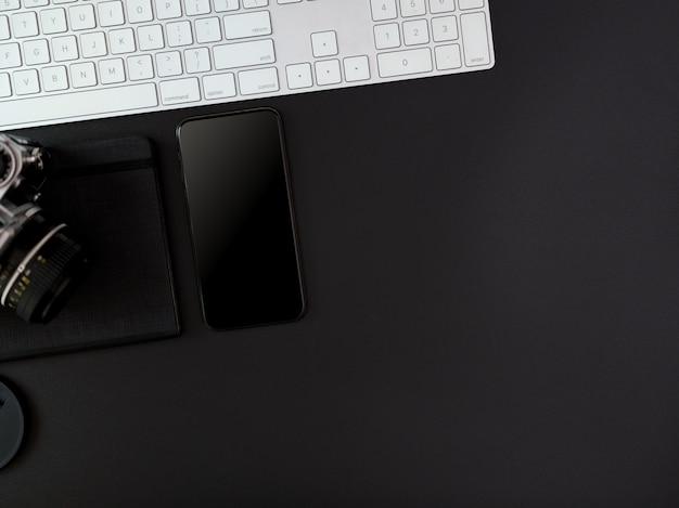 コンピューターのキーボード、スマートフォン、カメラ、スケジュール帳、コピースペースのある暗いモダンなオフィスデスク