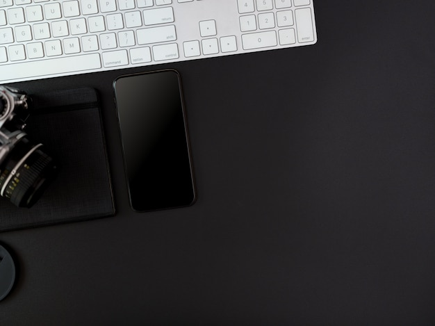 Dark modern office desk with computer keyboard, smartphone, camera, schedule book and copy space