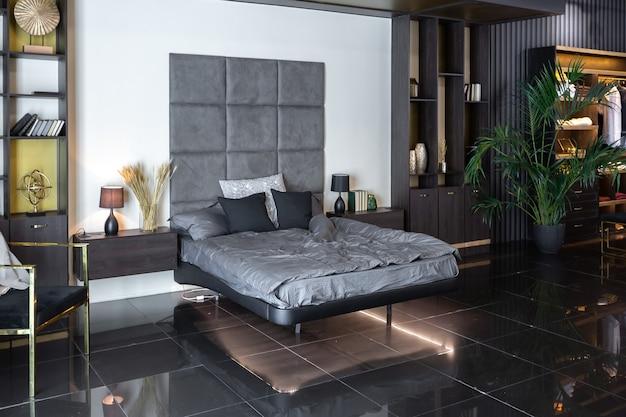 조명, 장식용 벽, 벽난로, 탈의실 및 거대한 창문이있는 어둡고 현대적인 세련된 남성 아파트 인테리어
