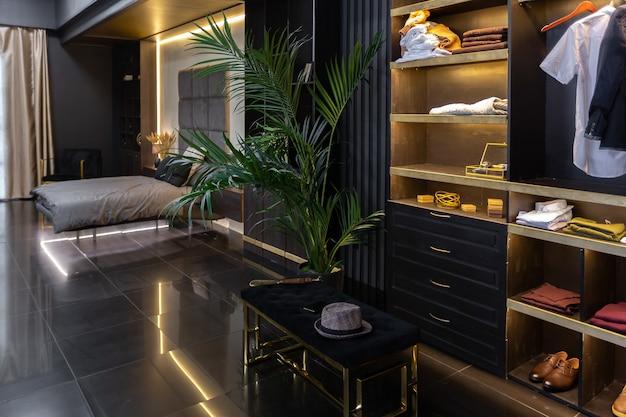 照明、装飾的な壁、暖炉、ドレッシングエリア、大きな窓を備えた暗いモダンでスタイリッシュな男性のアパートのインテリア