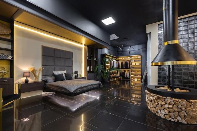 Темный современный стильный мужской интерьер квартиры с освещением, декоративными стенами, камином, гардеробной и огромным окном.