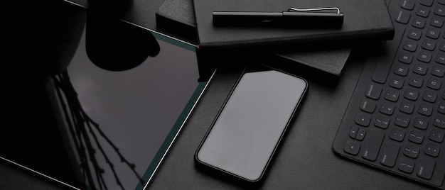 Dark modern workspace with digital tablet, smartphone, wireless keyboard, schedule books and pen