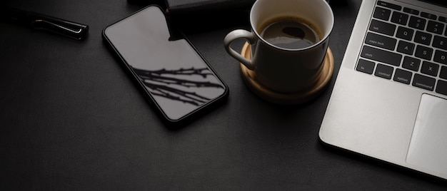 Dark modern workspace with laptop, smartphone, coffee cup, office supplies and copy space