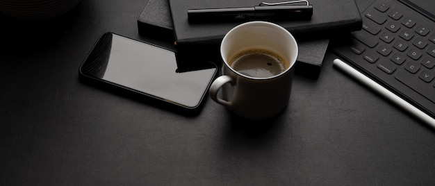 Dark modern workspace with tablet keyboard, smartphone, coffee cup, schedule books and copy space