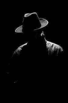 レトロなノワールスタイルの夜の帽子をかぶった男の暗い神秘的なシルエット