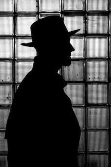 Темный мистический силуэт мужчины в шляпе ночью в стиле ретро нуар