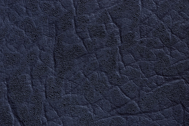 Dark navy blue leather textile with texture and pattern, closeup.