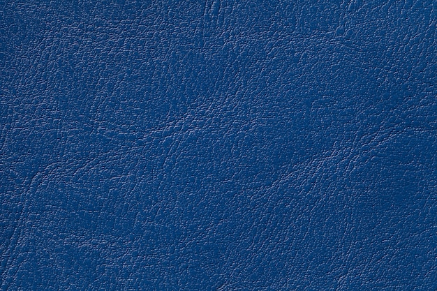 Dark navy blue leather texture background, closeup. denim cracked backdrop from wrinkle skin