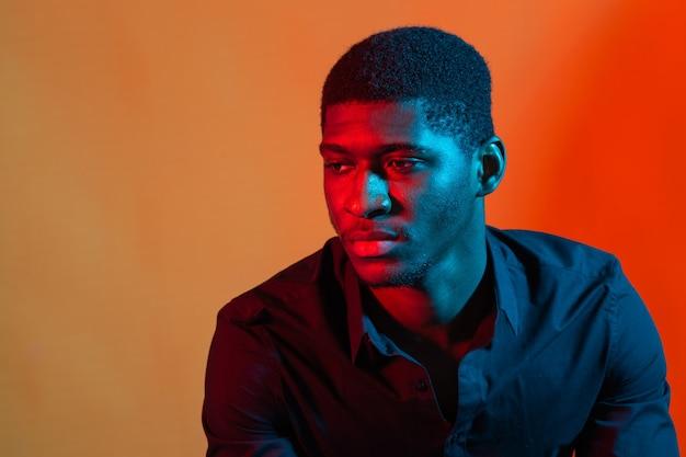 Темный неоновый портрет молодого человека в рубашке. красный и синий свет. технологии