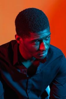 Темный неоновый портрет молодого человека в рубашке. красный и синий свет.