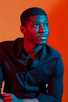 Dark neon portrait of young man wearing in shirt.