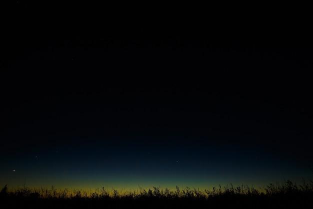 Темное ночное звездное небо на фоне сумеречного горизонта перед рассветом.