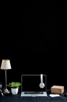 ノートパソコンと植物と暗いオフィスデスクテーブル