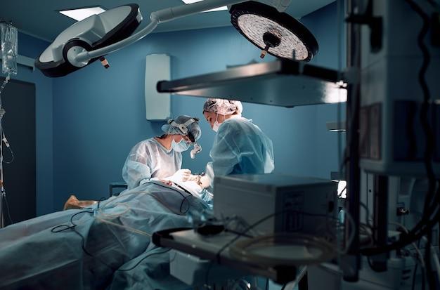 Темная операционная, хирурги делают сложную анкологическую операцию