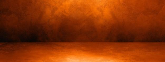 濃いオレンジ色のコンクリートインテリア背景バナー。空のテンプレートシーン