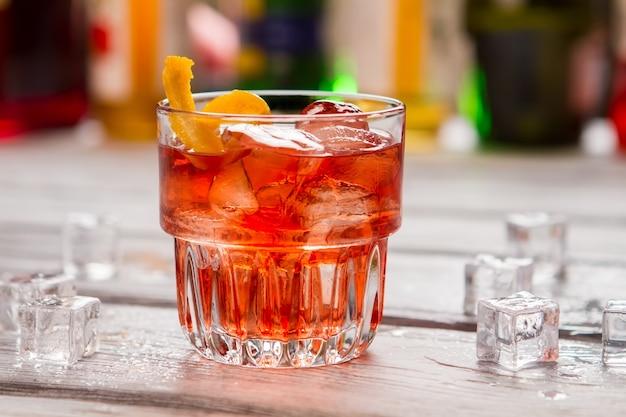 Темно-оранжевый напиток в стакане. кубики льда и цедра лимона. негрони подают в местном баре. вермут и джин.