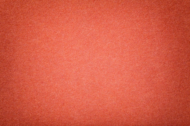 Dark orange matt suede fabric closeup. velvet texture of felt.