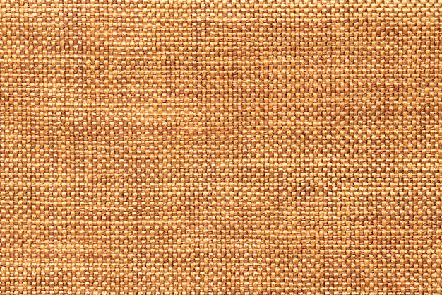 Dark orange textile background with checkered pattern, closeup. structure of the fabric macro.