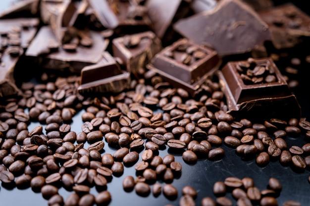 コンクリートの背景にダークオーガニックチョコレートとコーヒー豆。