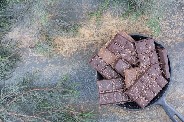 Una padella scura piena di cioccolatini a fette su fondo marmo. foto di alta qualità