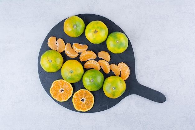 Una padella scura di mandarini acidi su bianco
