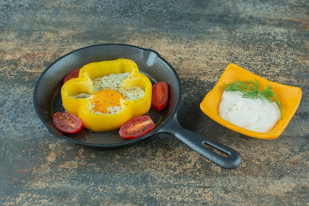 A dark pan with fried egg and tomato and sour cream on marble background