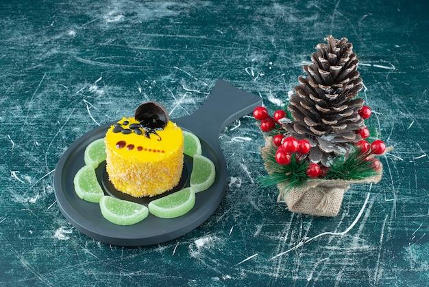 Una teglia scura con torta fresca gialla e grande pigna di natale. foto di alta qualità