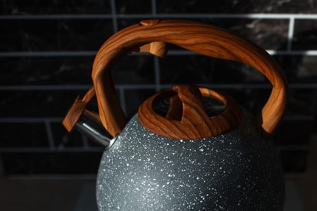 Темное фото современного стального чайника с деревянной ручкой. вид сверху крупным планом.
